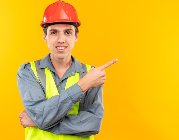 Glimlachende jonge bouwer man in uniforme punten aan de zijkant geïsoleerd op gele muur met kopieerruimte