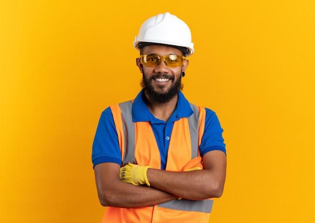 Glimlachende jonge bouwer man in veiligheidsbril dragen uniform met veiligheidshelm staande met gekruiste armen geïsoleerd op oranje muur met kopie ruimte