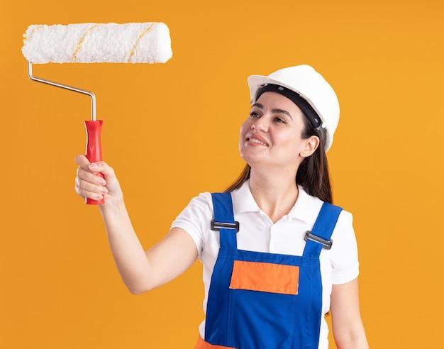 Glimlachende jonge bouwersvrouw in eenvormig die en rolborstel opheft bekijken die op oranje muur wordt geïsoleerd