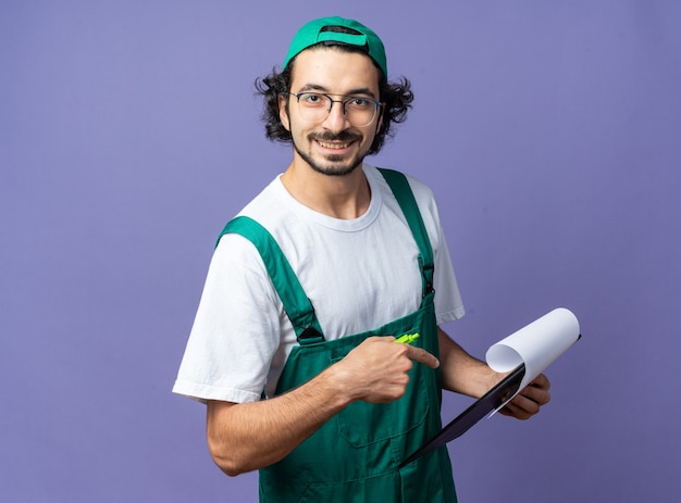 Glimlachende jonge bouwman die uniform draagt met pet vast en wijst naar klembord
