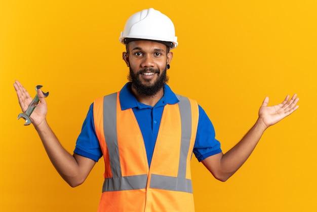 Glimlachende jonge bouwman in uniform met veiligheidshelm die de werkplaatssleutel vasthoudt en zijn hand open houdt geïsoleerd op een oranje muur met kopieerruimte