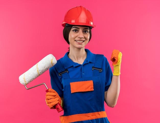 Glimlachende jonge bouwvrouw in uniform die handschoenen draagt die een rolborstel houden die ja gebaar toont dat op roze muur wordt geïsoleerd