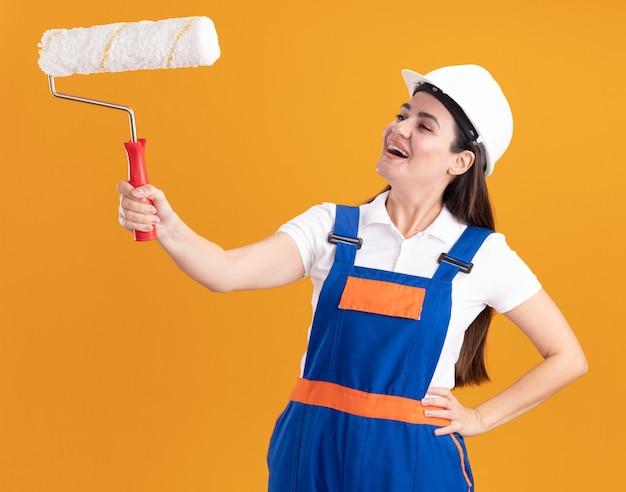 Glimlachende jonge bouwvrouw in uniform die opheft en kijkt naar de rolborstel die de hand op de heup legt, geïsoleerd op een oranje muur