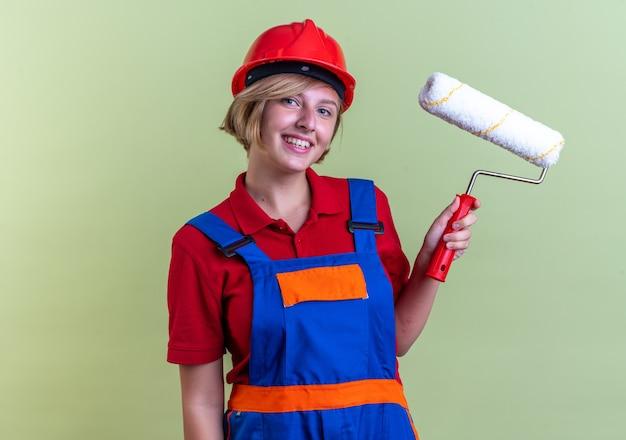 Glimlachende jonge bouwvrouw in uniform met rolborstel geïsoleerd op olijfgroene muur