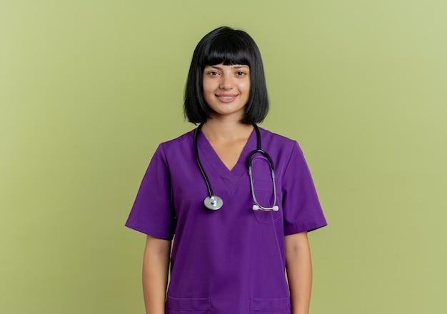 Glimlachende jonge brunette vrouwelijke arts in uniform met stethoscoop stands geïsoleerd op olijfgroene achtergrond met kopie ruimte