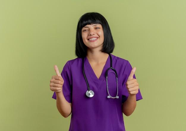 Glimlachende jonge brunette vrouwelijke arts in uniform met stethoscoop thumbs up met twee handen geïsoleerd op olijfgroene achtergrond met kopie ruimte