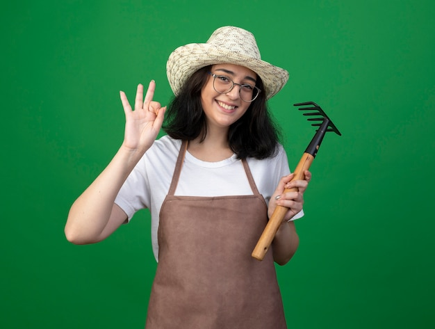 Glimlachende jonge brunette vrouwelijke tuinman in optische bril en uniform dragen tuinieren hoed gebaren ok handteken en houdt hark geïsoleerd op groene muur