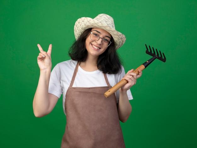 Glimlachende jonge brunette vrouwelijke tuinman in optische bril en uniform dragen tuinieren hoed houdt hark en gebaren overwinning handteken geïsoleerd op groene muur