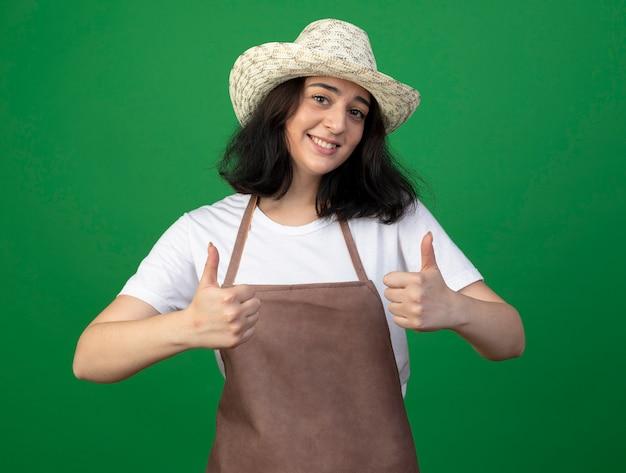 Glimlachende jonge brunette vrouwelijke tuinman in optische glazen en uniform dragen tuinieren hoed duimen omhoog van twee handen geïsoleerd op groene muur