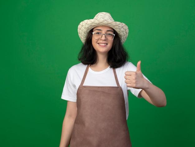 Glimlachende jonge brunette vrouwelijke tuinman in optische glazen en uniform dragen tuinieren hoed thumbs up geïsoleerd op groene muur