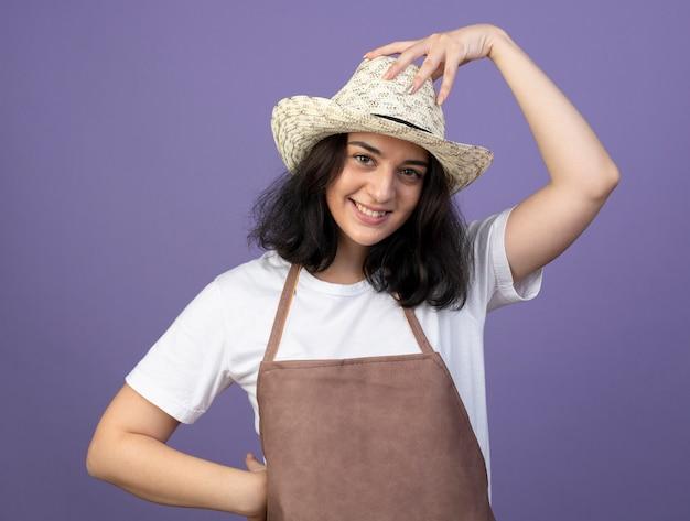 Glimlachende jonge brunette vrouwelijke tuinman in uniform dragen en zetten hand op tuinieren hoed geïsoleerd op paarse muur