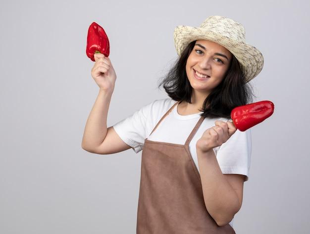 Glimlachende jonge brunette vrouwelijke tuinman in uniform dragen tuinieren hoed houdt rode paprika geïsoleerd op een witte muur met kopie ruimte