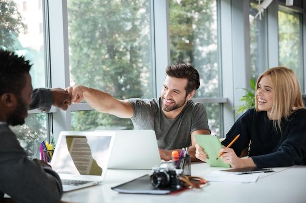 Glimlachende jonge collega's die in bureaucoworking zitten