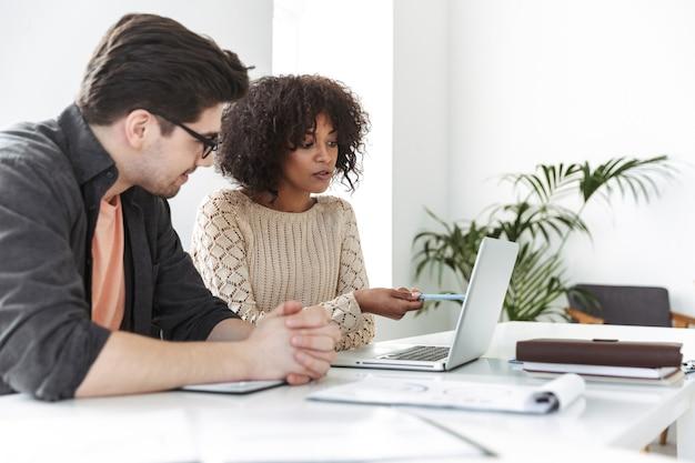 Glimlachende jonge collega's die samen laptopcomputer gebruiken terwijl ze bij de tafel op kantoor zitten
