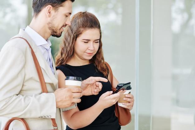 Glimlachende jonge collega's drinken afhaalmaaltijden koffie en bespreken nieuwe applicatie op smartphone