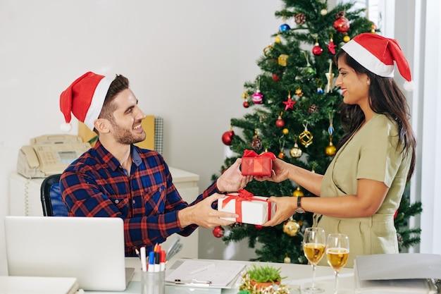 Glimlachende jonge collega's in handen van de kerstman uitwisselen van kerstcadeautjes in kantoor