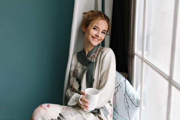 Glimlachende jonge dame met kopje koffie, thee in haar had, zittend op de vensterbank, goedemorgen ontspannen. het dragen van zijden pyjama's in bloemen, heeft blond haar. foto in turquoise kleuren.