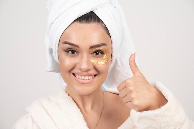 Glimlachende jonge donkerbruine vrouw die badjas met kosmetische ooglapjes draagt.