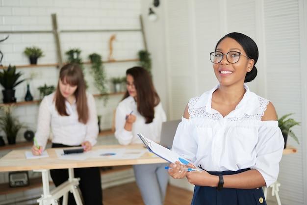 Glimlachende jonge donkerhuidige vrouw staat in een modern kantoor met haar collega's op de achtergrond