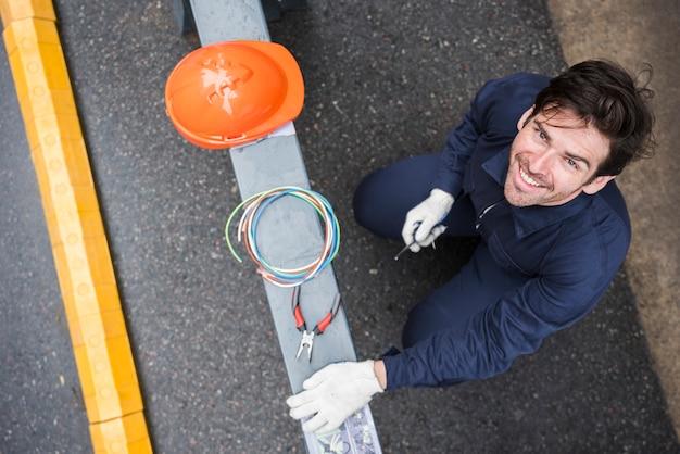 Glimlachende jonge elektricien die omhoog met holdings elektrisch instrument kijken