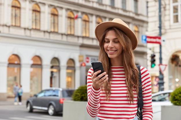 Glimlachende jonge europese vrouw geniet van recreatietijd, bekijkt interessante video op website, draagt stijlvolle hoofddeksels en gestreepte trui