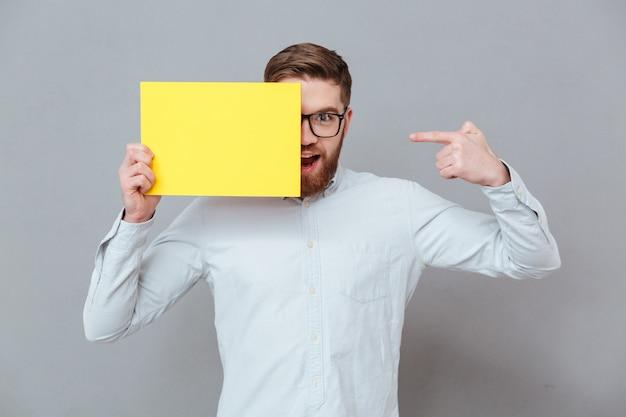 Glimlachende jonge gebaarde zakenman die leeg document houdt