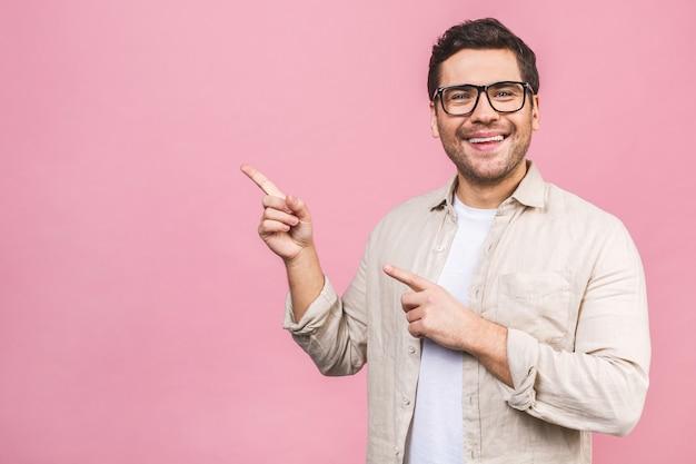 Glimlachende jonge geïsoleerde mens. stijlvolle man met bril, wijzende vinger.