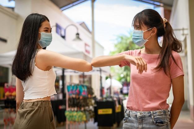 Glimlachende jonge, gezonde vrouwelijke collega's van gemengd ras die medische gezichtsmaskers dragen die elkaar begroeten door ellebogengebaar te stoten op de werkplek en sociale afstand te houden, waardoor verspreiding van het covid19-virus wordt voorkomen
