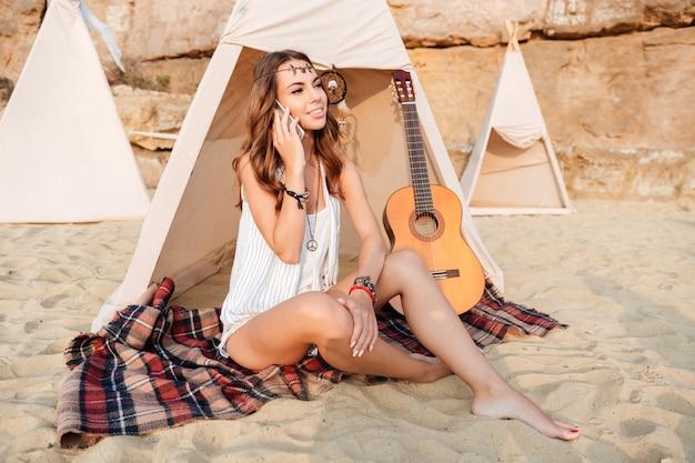 Glimlachende jonge hippievrouw in tipi op het strand
