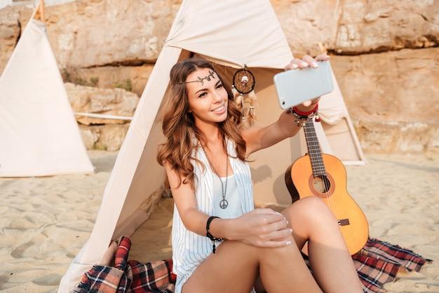 Glimlachende jonge hippievrouw in wigwam op het strand