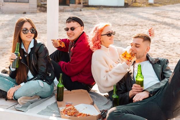 Glimlachende jonge hipsters die op grond met bier en pizza zitten