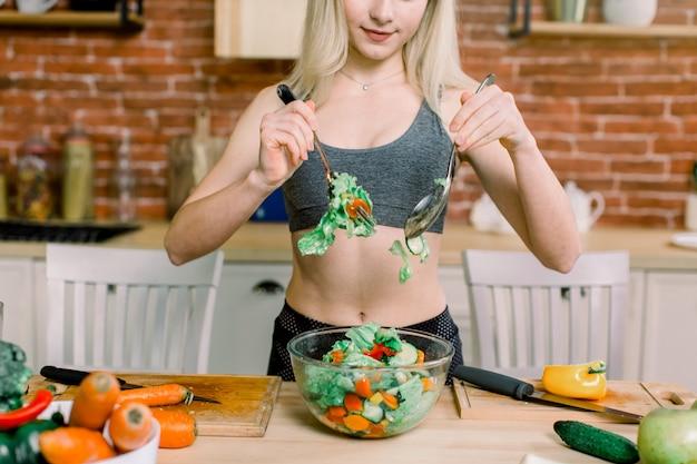 Glimlachende jonge huisvrouw die verse salade mengt. gezonde levensstijl en eten. eetpatroon. dieet concept. gezond eten. welzijn, wellness.