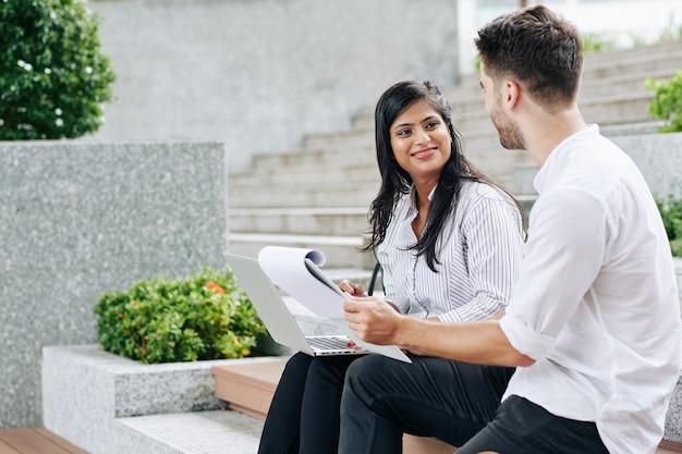 Glimlachende jonge indische vrouw die pratende collega met marketingrapport in handen bekijkt