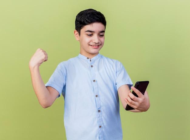 Glimlachende jonge jongen die en mobiele telefoon houdt bekijkt die sterk gebaar doet dat op olijfgroene muur wordt geïsoleerd