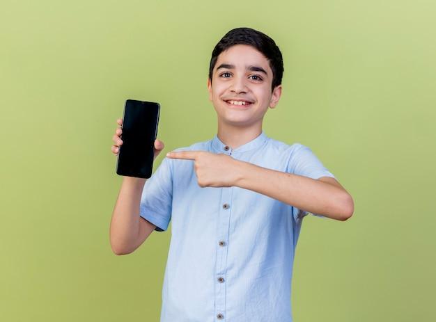 Glimlachende jonge jongen die en op mobiele telefoon toont richt die voorzijde bekijkt die op olijfgroene muur wordt geïsoleerd