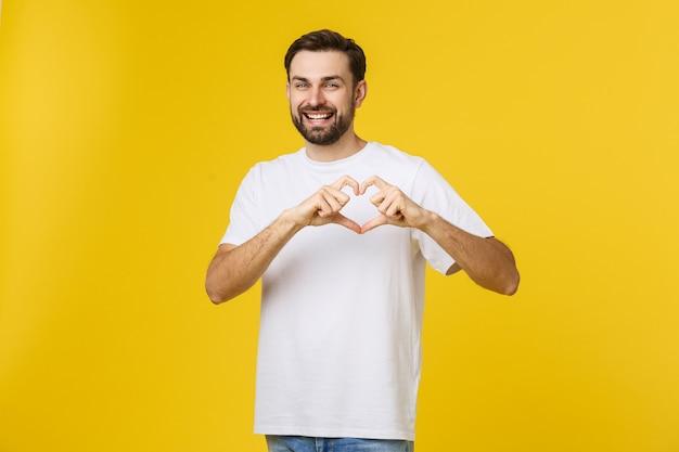 Glimlachende jonge jongen die hartgebaar op zijn borst met wit overhemd maakt dat op gele ruimte wordt geïsoleerd