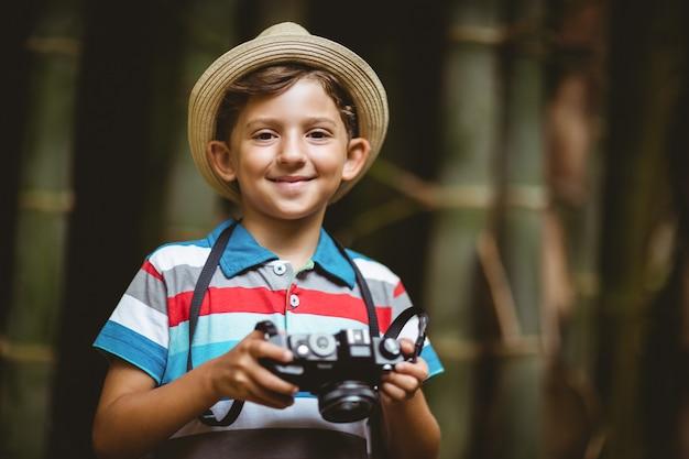 Glimlachende jonge jongen die in hoed een camera houdt