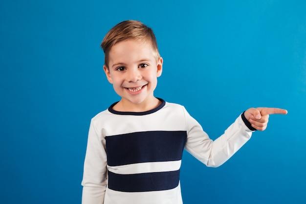 Glimlachende jonge jongen die in sweater weg richt