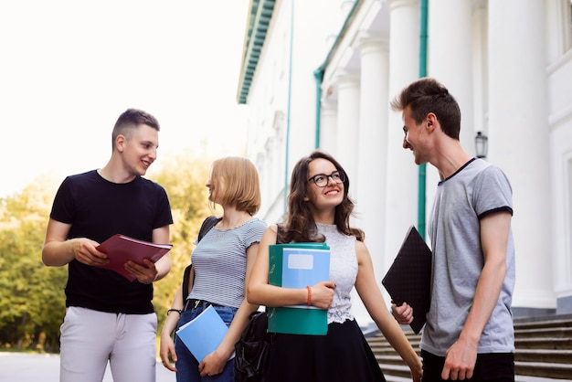 Glimlachende jonge jongen en meisje hebben een gesprek, terwijl een ander stel in de buurt er tevreden uitziet en met elkaar flirt