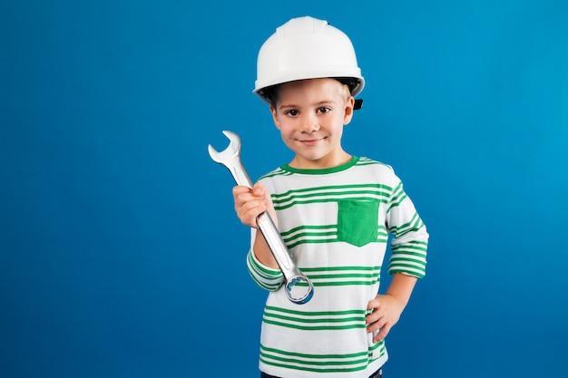 Glimlachende jonge jongen in het beschermende helm stellen met moersleutel