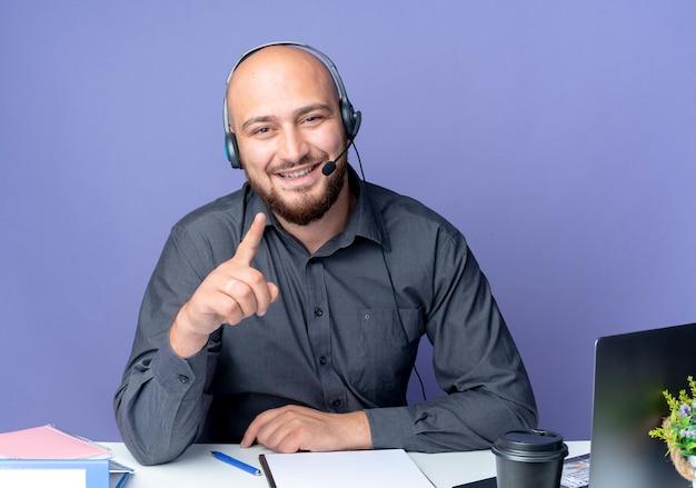 Glimlachende jonge kale callcentermens die hoofdtelefoonszitting bij bureau met uitrustingsstukken draagt ?? die vinger opheft en hand op bureau zet dat op purpere muur wordt geïsoleerd