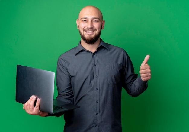 Glimlachende jonge kale de holdingslaptop van de callcentermens en het tonen van duim omhoog geïsoleerd op groene muur