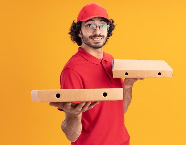 Glimlachende jonge kaukasische bezorger in rood uniform en pet met een bril die in profielweergave staat en pizzapakketten vasthoudt en uitrekt die op een oranje muur zijn geïsoleerd