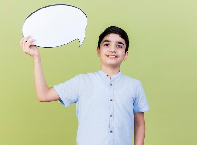 Glimlachende jonge kaukasische de toespraakbel die van de jongensholding camera bekijken die op olijfgroene achtergrond met exemplaarruimte wordt geïsoleerd