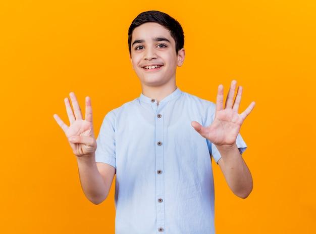 Glimlachende jonge kaukasische jongen die camera bekijkt die negen met handen bekijkt die op oranje achtergrond worden geïsoleerd