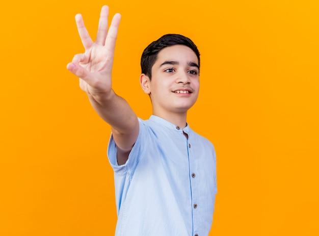 Glimlachende jonge kaukasische jongen die zich in profielmening bevindt die drie met hand toont die kant bekijkt die op oranje achtergrond met exemplaarruimte wordt geïsoleerd