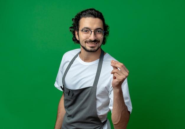 Glimlachende jonge kaukasische mannelijke kapper die glazen en golvende haarband draagt in uniform die geldgebaar doet dat op groene achtergrond met exemplaarruimte wordt geïsoleerd