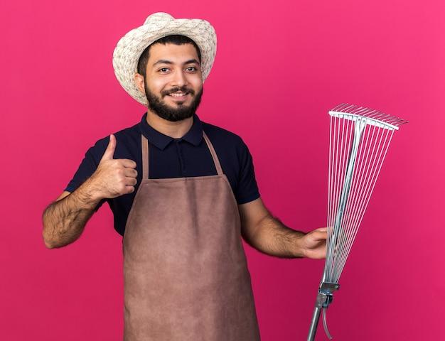 Glimlachende jonge kaukasische mannelijke tuinman die een tuinhoed draagt, houdt bladhark en duimen omhoog geïsoleerd op roze muur met kopieerruimte