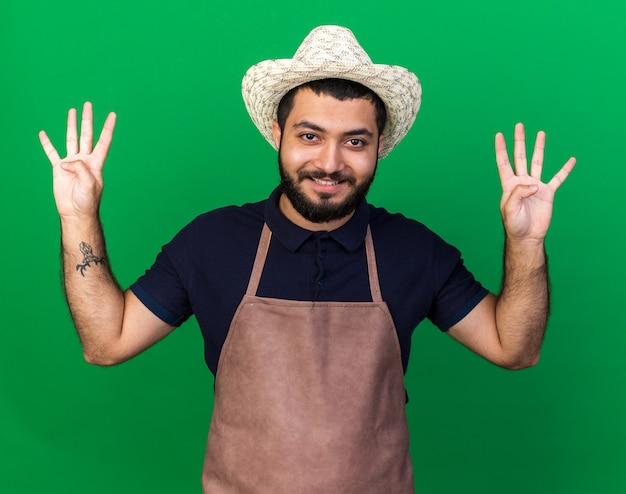 Glimlachende jonge kaukasische mannelijke tuinman die tuinierhoed draagt die acht met vingers gebaart die op groene muur met exemplaarruimte worden geïsoleerd