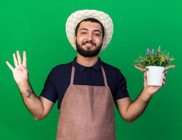 Glimlachende jonge kaukasische mannelijke tuinman die tuinierhoed draagt die bloempot houdt en vier met vingers gebaart die op groene muur met exemplaarruimte worden geïsoleerd